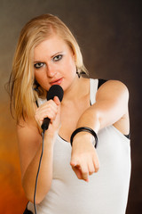 Blonde woman singing to microphone