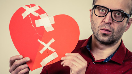 Adult man holding broken heart