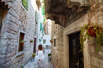 Young brown-haired woman in white hat and dress walking the narrow street of the old city