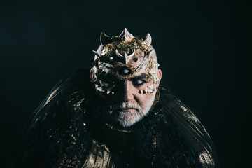 Horror and fantasy concept. Alien, demon, sorcerer makeup. Man with third eye, thorns or warts. Demon on black background, copy space. Senior man with white beard dressed like monster in darkness.