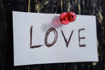 written love on a piece of paper and attached to the blackboard