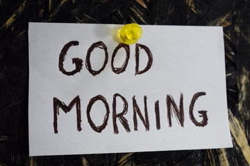 Good Morning is written on a sheet of white paper