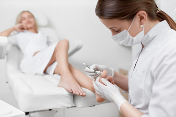 Podiatrist doctor caring about client foot with special iron tool.