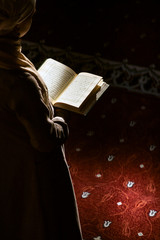 Muslim woman under the sunlight reading quran in a mosque