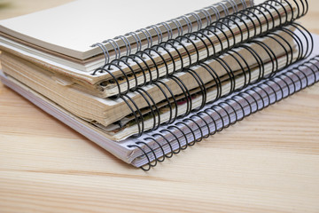 Pile of different notebooks lying on wooden table