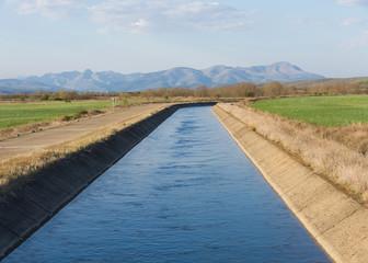 Canal de agua para el riego en paisaje con montañas al fondo