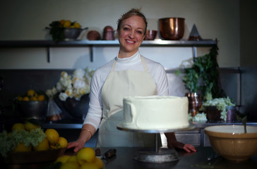 Claire Ptak, owner of Violet Bakery in Hackney, east London, poses for a portrait with a tier of the cake for the wedding of Prince Harry and Meghan Markle in the kitchens at Buckingham Palace in London