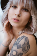 Close up portrait of blonde hipster girl with piercing and tattoos wearing black hat looking at the camera