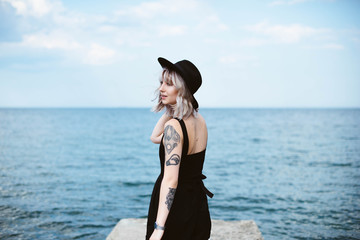 Beautiful blonde hipster girl with tattoos wearing black dress and hat standing on the concrete pier on the sea. Outdoors