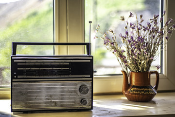 Old Vintage Radio staying near window and next to teapot with wild flowers. Morning light.