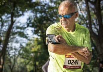 Senior runner using a fitness tracker application