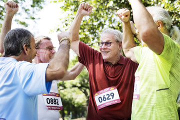 Group of cheerful senior runners at the park