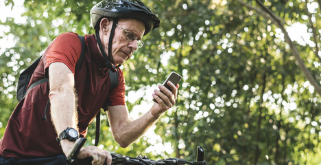 Senior cyclist using the gps on his phone
