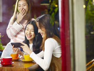 three young asian women looking at mobile phone and laughing in coffee shop