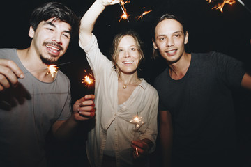 Two Caucasian men and a woman playing with sparklers celebration and festive party concept