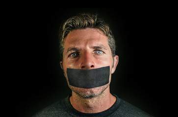 young man with mouth and lips sealed covered with adhesive tape in censorship coerced freedom of speech and forced silence and secrecy