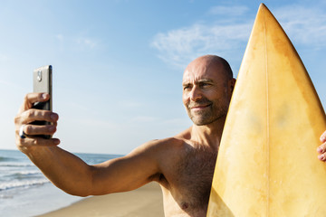 Man holding surfboard taking selfie