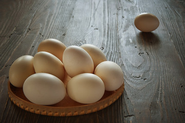 A pile of chicken eggs on an old wooden table