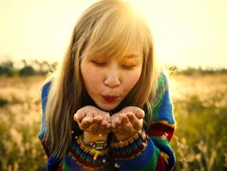 Woman blowing flower petals off her hands