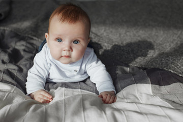 Happy blond infant with blue eyes in bed sports and smiling