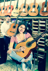 Couple playing guitars in music shop.
