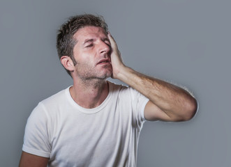 portrait of sad and depressed man with hand on face looking desperate feeling frustrated and helpless in depression and sadness facial expression