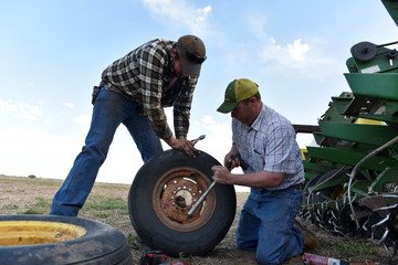 Farmhand Andrew Weaver and cotton farmer Drew Malchoff work to replace a flat tire on a planting implement in Wakita, Oklahoma