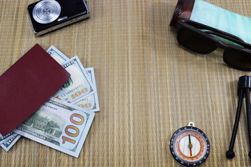 passport with money (dollars) for vacation, camera, glasses and different things on the table