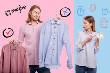 Late for work. Relaxed young man choosing a shirt and being late for work while his emotional worried wife pointing to the clock