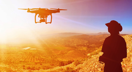 Quadrocopters silhouette against the background of the sunset. Flying drones in the evening sky