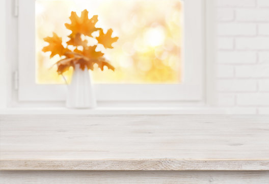 Bleached wooden table on the background of white autumn windowsill