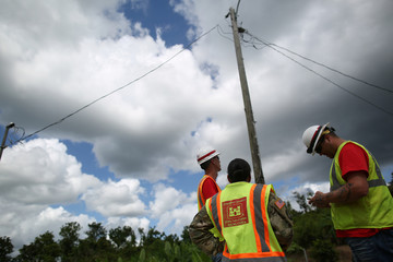 Members of the U.S. Army Corps of Engineers stand underneath an electricity pole, as the island's fragile power system is still reeling from the devastation wrought by Hurricane Maria eight months ago, in Utuado