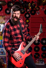 Guitarist on shouting face playing electric guitar on stage