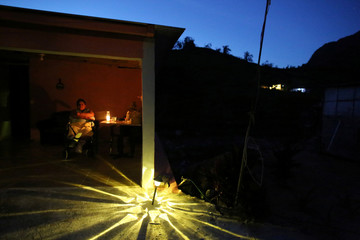 Gladys Lugo, sits in a wheelchair as a solar lamp illuminates the entrance of her home as the island's fragile power system is still reeling from the devastation wrought by Hurricane Maria eight months ago, in Jayuya