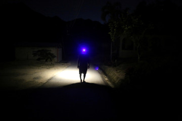Jose Alvarez uses a head lamp while walking in the dark as the island's fragile power system is still reeling from the devastation wrought by Hurricane Maria eight months ago, in Jayuya