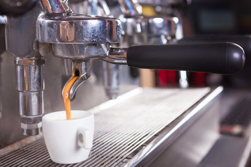 Close up of traditional Espresso Coffee Machine making cup of espresso coffee.
