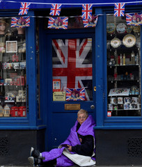 A royal fan sits covered in her sleeping bag having spent the night on the pavement outside of  Windsor Castle, the location for the forthcoming wedding of Britain's Prince Harry and his fiancee Meghan Markle, in Windsor, Britain