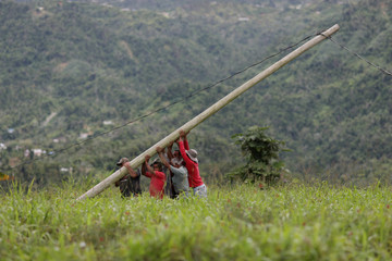 Residents of La Chorrera neighbourhood work on an electricity pole as the island's fragile power system is still reeling from the devastation wrought by Hurricane Maria eight months ago, in Utuado
