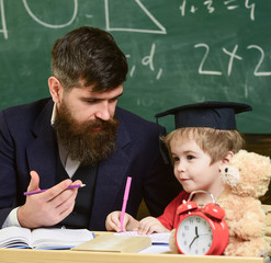 Nursery teacher and little child drawing picture. Teacher in formal wear and pupil in mortarboard in classroom, chalkboard on background. Father teaches son, discuss, explain. Education concept.