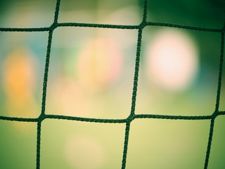 Detail on a soccer net and ball waiting on turf. Soccer goal.