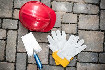 red helmet, trowel and work gloves