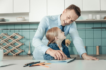 Child upbringing. Happy male person keeping smile on face and bowing head while studying with his daughter