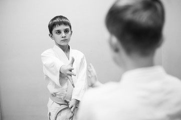 Boys in a kimono have an aikido training with a coach