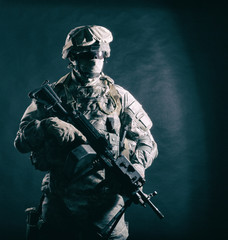 United States Marine Corps ranger, special forces soldier, security serviceman in battle uniform, armed with machine gun hiding his face with balaclava and glasses studio shot on black background