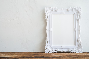 White vintage photo frame on old wooden table over white wall background