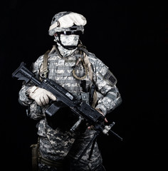 Marine with hiding identity, protected with helmet and body armour in digital camouflage combat uniform posing with light machine gun equipped infrared laser aiming light isolated on black background