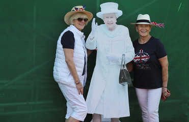 Two women pose for a picture with a cardboard cut out of Britain's Queen Elizabeth a day before Prince Harry and Meghan Markle's wedding at Windsor Castle, Windsor