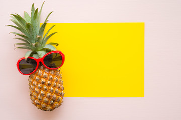 Flat lay of pineapple with red sunglasses on yellow and pink background with copy space, tropical summer holiday vacation, wedding invitation party concept