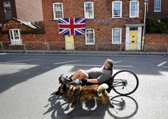 A man rides a recumbent bicycle as he walks his dog past houses decked out in Union flags and bunting a day before the wedding of Britain's Prince Harry and Meghan Markle in Windsor