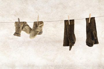 Two pairs of knitted woolen socks hanging on a laundry rope with wooden clothespins